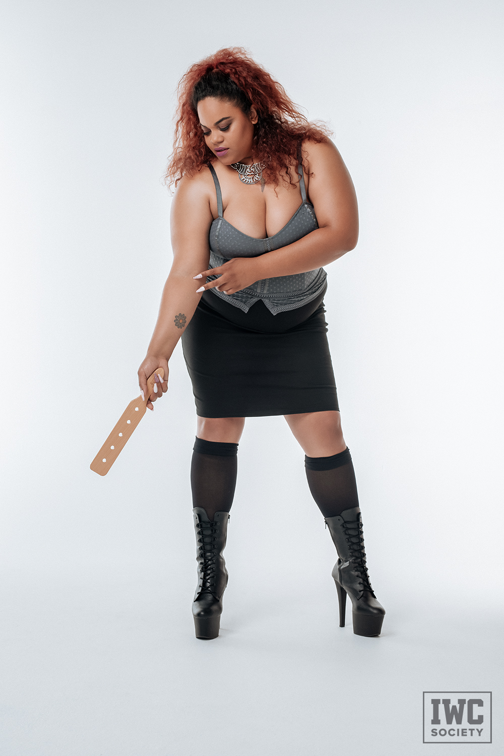 bbw femdom Ms Charmness holding a paddle wearing a low cut top black skirt and black boots