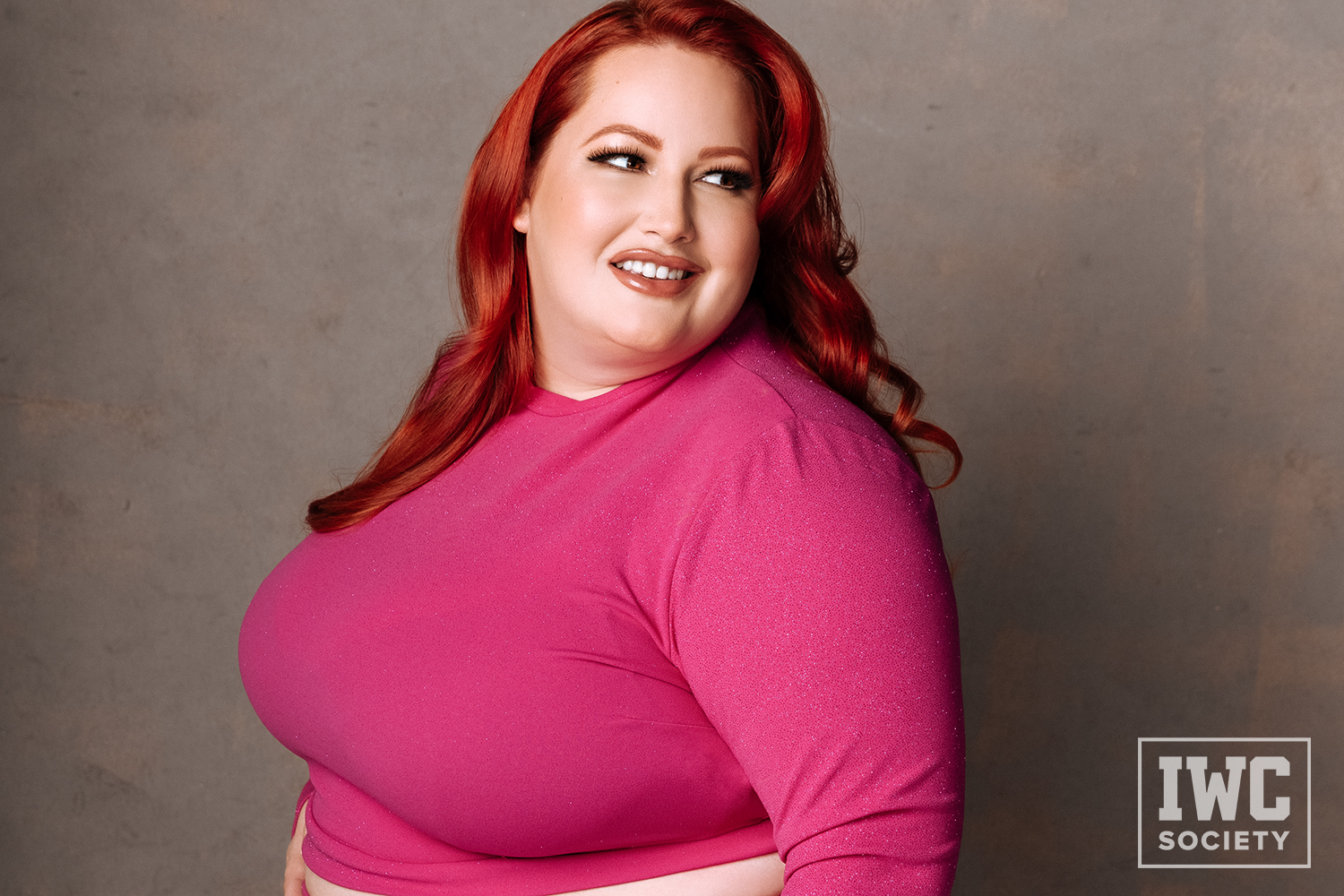 Eliza Allure BBW redhead glamour shot staring over shoulder with slight smile on face