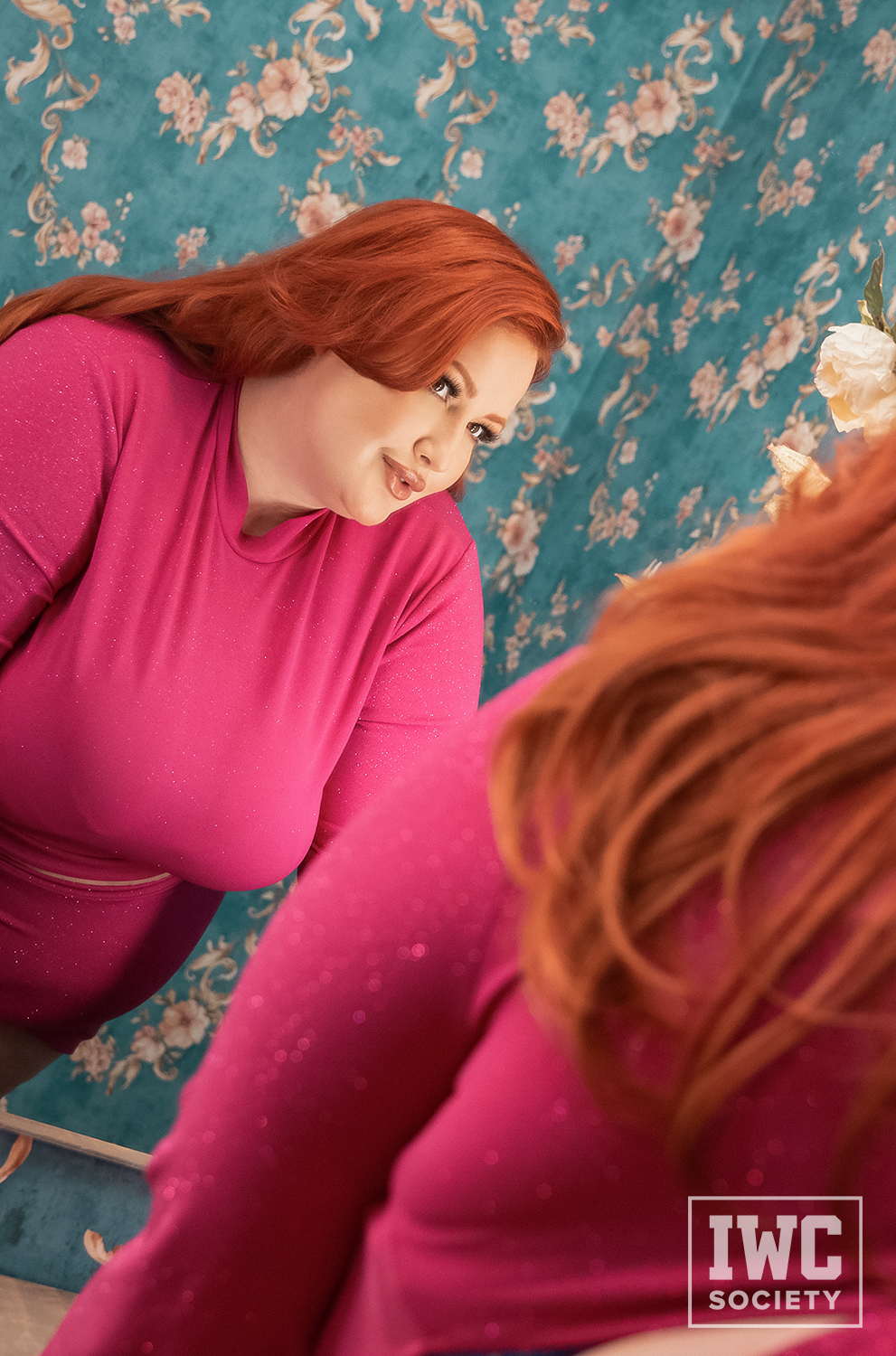 Eliza Allure BBW in bright dress and red hair staring at reflection