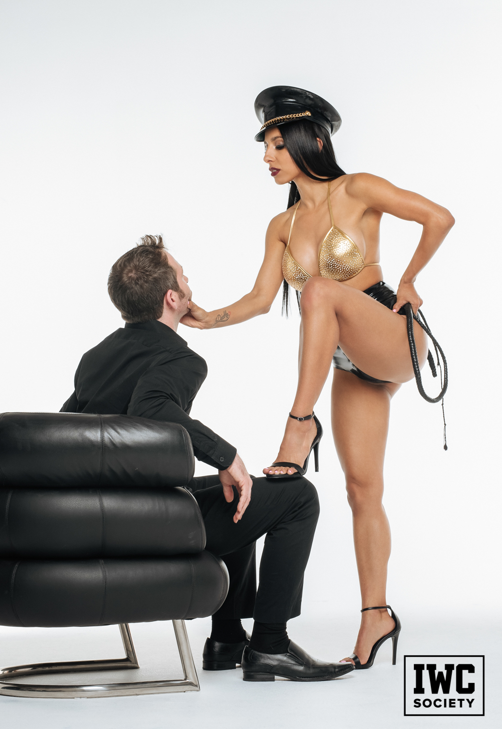 Brunette domme grabbing mans face with tattoo and heels