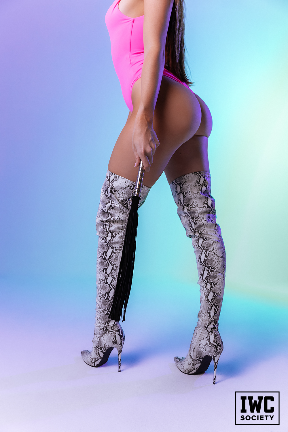 Thigh high snake boots with heels holding whip