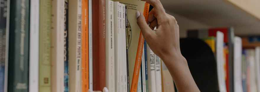 person holding a book on wooden shelf