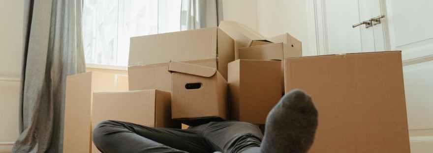person in black pants sitting on brown cardboard box