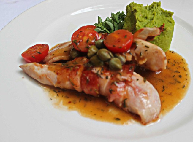 Rabbit fillet wrapped in bacon, with cerry tomatoes and cappers.