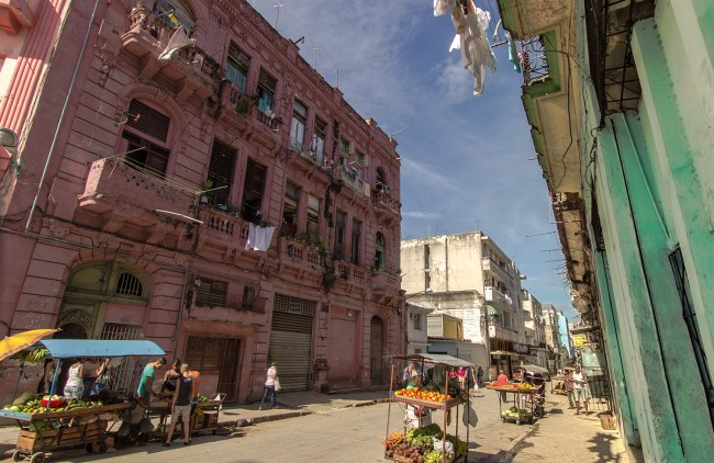 A street in Havana with fruit stands on each side of the street. There very old buildings that serve as apartments for large families. Outside each apartment window there are pieces of clothing hanging out.