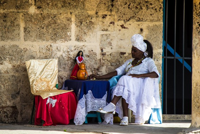 An Afro-Cuban woman sitting in the plaza selling her Santeria services.