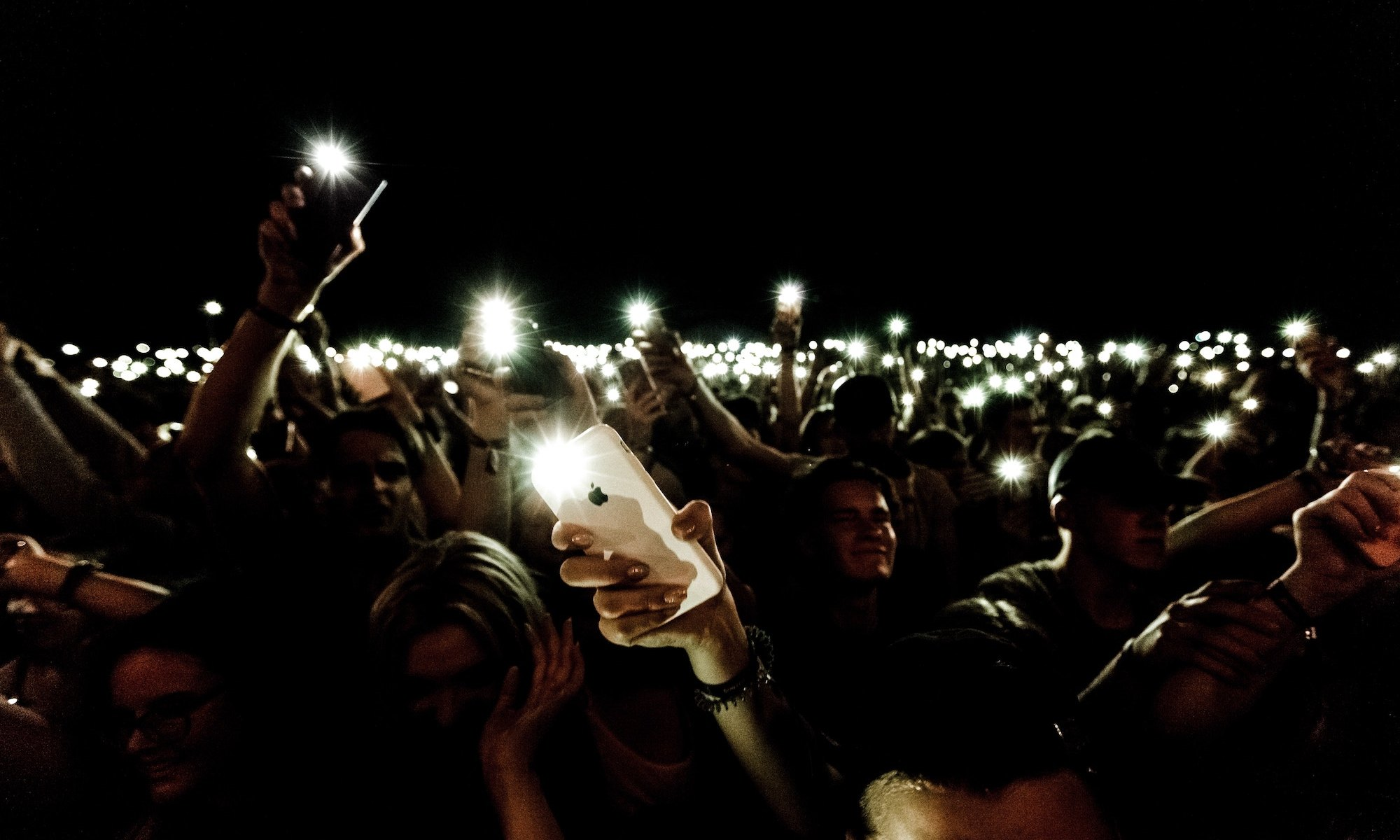 Large crowd of people at a night, outdoor event holding their smartphones over their heads and taking flash pictures.