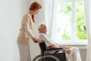 Smiling nurse supporting disabled senior man in the wheelchair