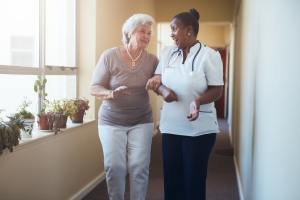 Happy healthcare worker walking and talking with senior woman