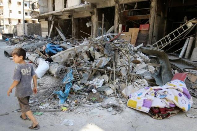 A boy walks past damaged shops in the rebel held Tariq al-Bab neighborhood of Aleppo, Syria, August 22, 2016. REUTERS/Abdalrhman Ismail
