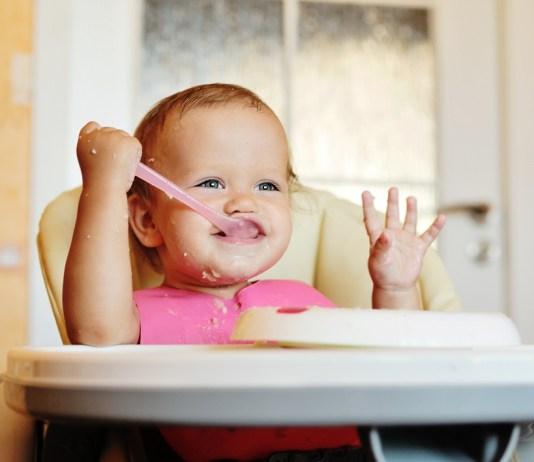 kisbaba nevetve eszik kanallal