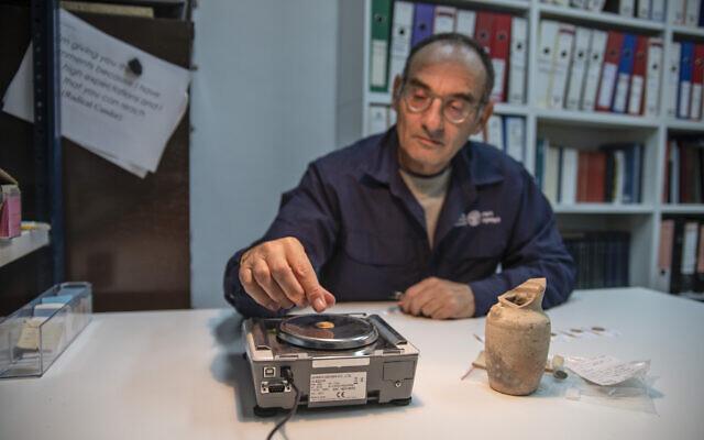 Dr. Robert Cole lemér egy aranyérmét, amelyet Jeruzsálem nyugati falánál találak - fotó: Shai Halevi / Izraeli Régészeti Hatóság