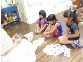 女の子3名がカードで遊びながら学習している様子
