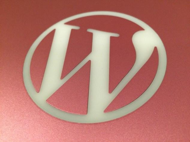 WordPress logo on pink MBP