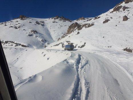 trucks driving across snowy landscape