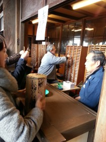 During the New Year Days the Japanese get a fortune for the upcoming year. Unfortunately in these kinds of fortune places one is able to get the fortune only in Japanese. The people shake the box and then the man gets a fortune from the shelf.