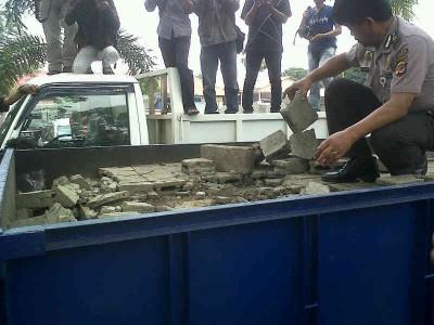 Anggota polisi sedang memeriksa truk yang mengangkut batako, Rabu (19/2).  Di dalam batako tersebut tersembunyi tangki untuk menyedot ribuan liter solar. (JABARTODAY/AVILA DWIPUTRA)