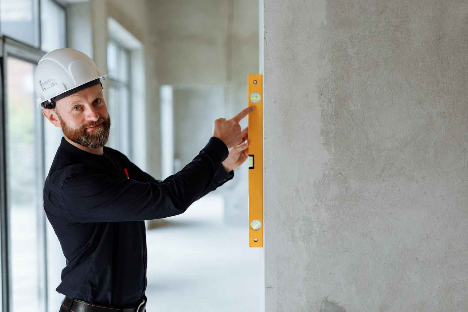 an engineer holding a spirit level against a wall