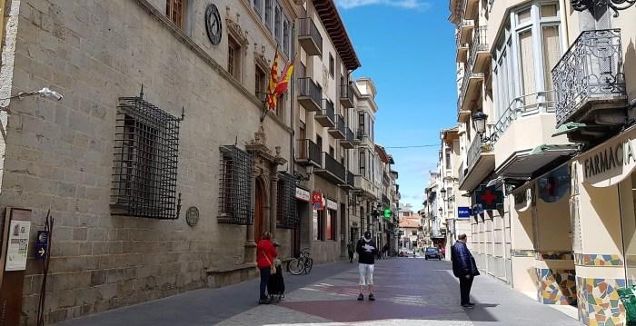 AYUNTAMIENTO. Vox Jaca pide que las banderas oficiales ondeen a media asta. En la imagen, el Ayuntamiento de Jaca. En primer plano, ciudadanos manteniendo las medidas de seguridad contra el coronavirus, esperando su turno para entrar en la famacia. (FOTO: Rebeca Ruiz)