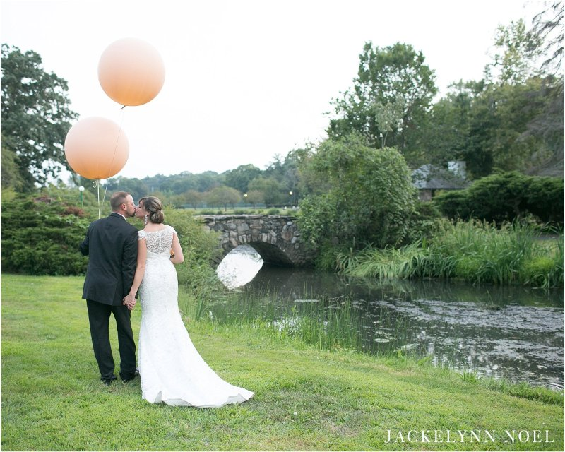 Leila and Matt leaning in for a kiss and Matt's holding the blush round balloons.