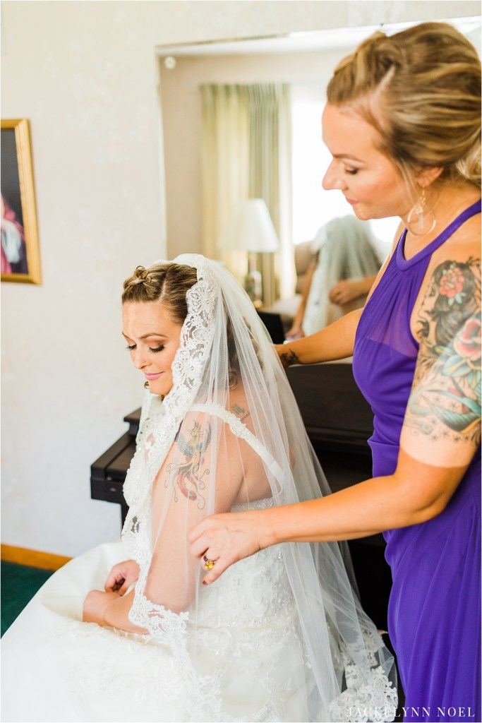 Lisa's bridesmaid helps her put in her veil