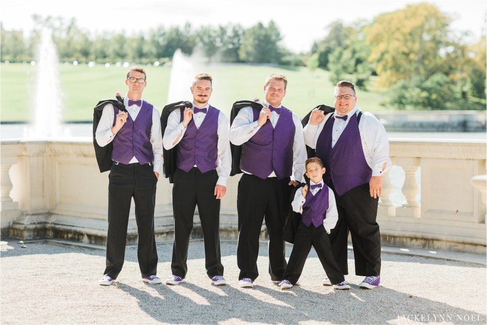 Portrait of the Groom and groomsmen in front of the grand basin with purple vests on