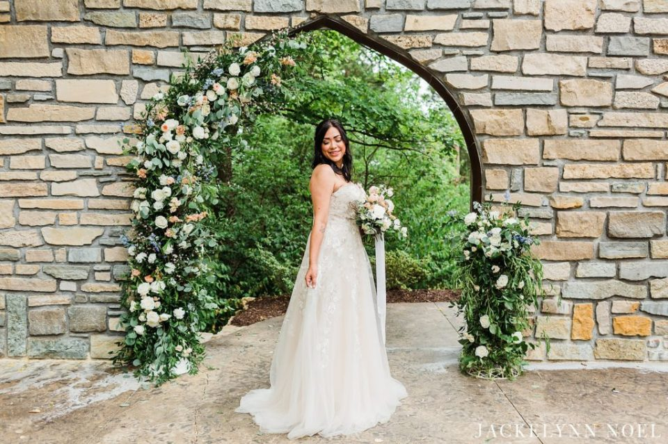 Bride wearing a strapless wedding gown holding spring bouquet.