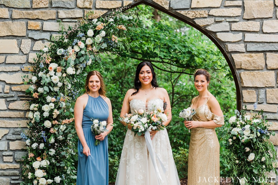 Bride wearing a strapless wedding gown holding spring bouquet. The bride is standing in front of her bridesmaids wearing dusty blue and gold at the stone wall at Haue Valley Wedding Venue.