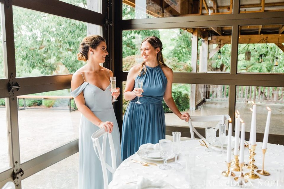 Bridesmaids wearing dusty blue standing in the wedding venue next to an all white table.