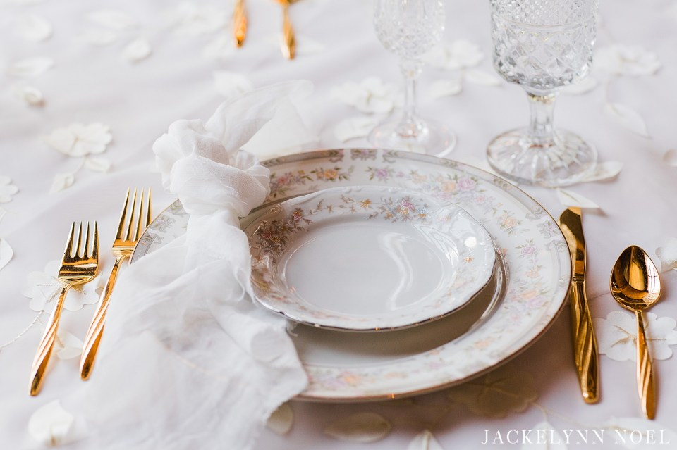 White china with gold flatware.