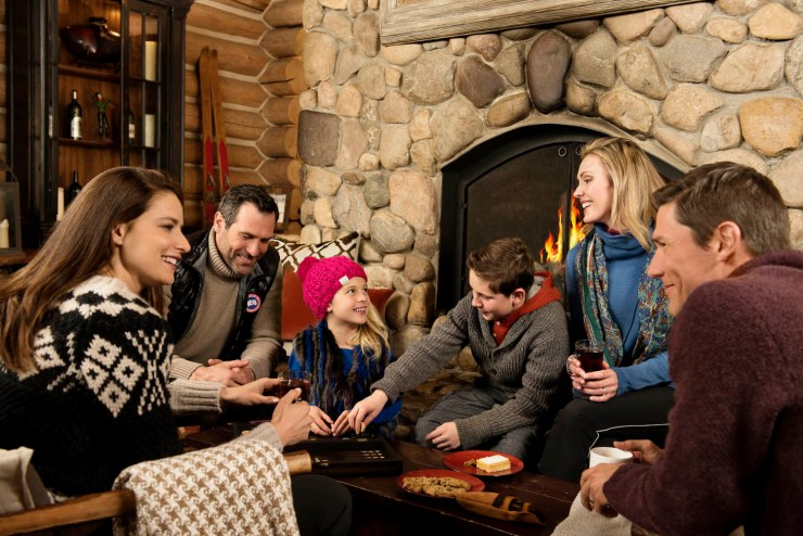 Family playing games around fireplace