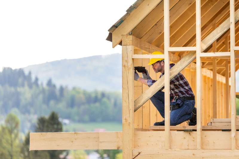 roofer-builder-working-on-roof-structure-at-constr-6AHKKP3.jpg