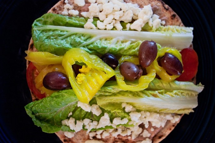 pita sandwich with feta, romaine, greek olives, yellow pickled peppers, and tomatoes