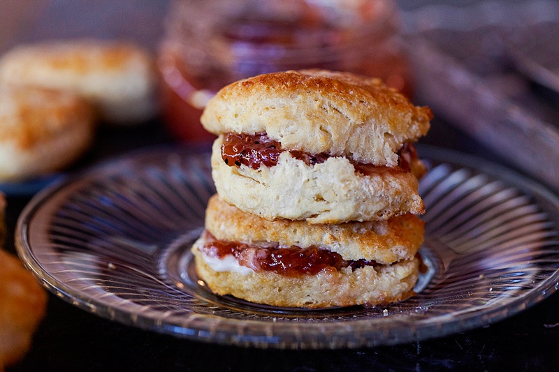 two buttermilk biscuits served with butter and jam