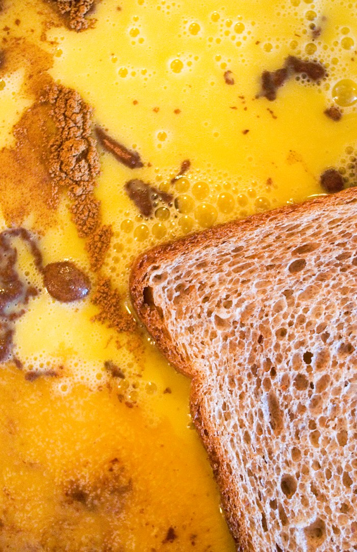whole grain bread floating in egg and cinnamon french toast batter