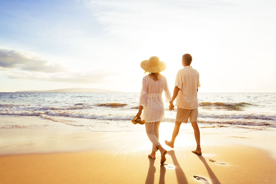 Walking without Knee Pain. Happy Romantic Middle Aged Couple Enjoying Beautiful Sunset Walk on the Beach. Travel Vacation Retirement Lifestyle Concept
