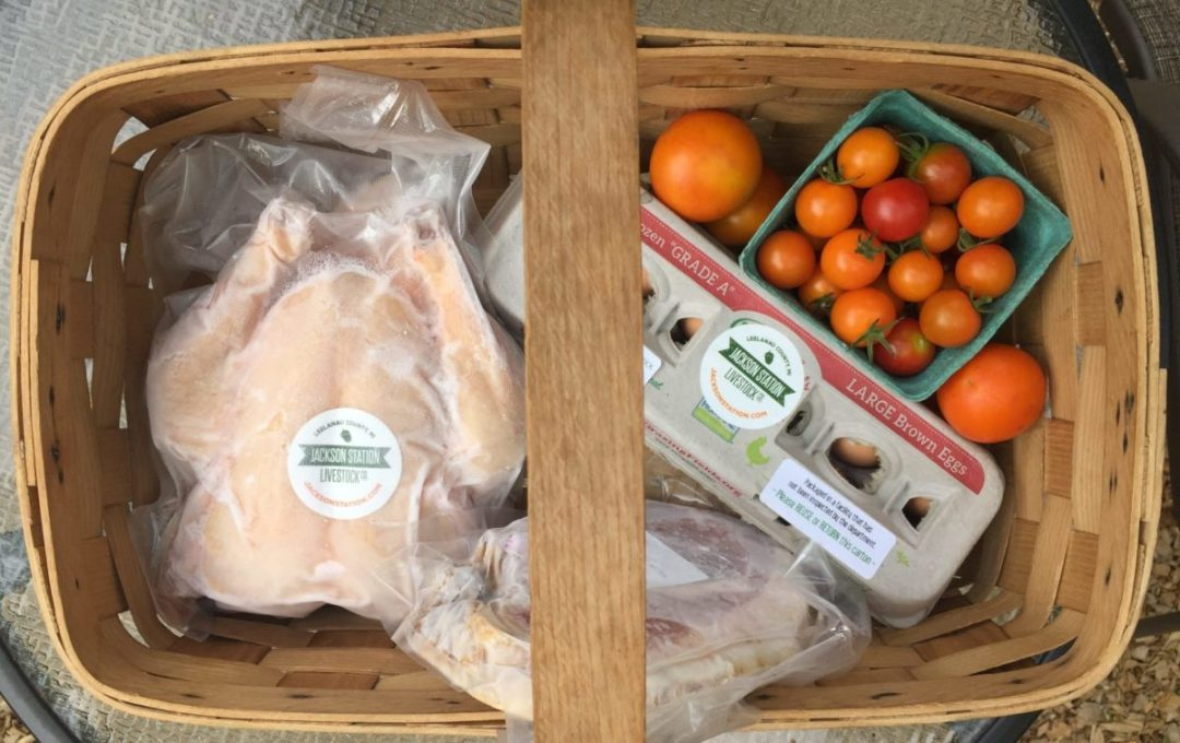 basket of farm fresh chicken, eggs and tomatoes