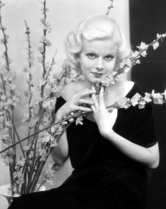 4th January 1933: American actress Jean Harlow (1911 - 1937) clasps a spray of flowers to her bosom.