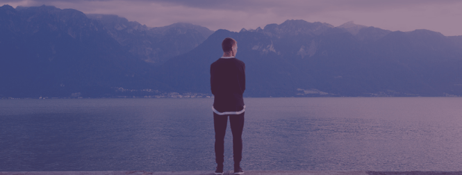 Image of a man looking off into the distance. There is a lake and mountain range.