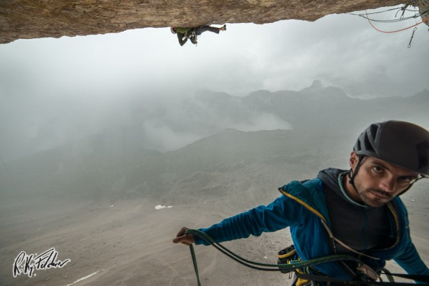 """Trying the crux pitch of """"Pan Aroma"""" (Tre Cime) in the rain - Credits: Riky Felderer"""