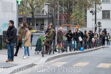 Covid 19 Pandemic Crisis – Group of people line up at food shop – 7 April 2020