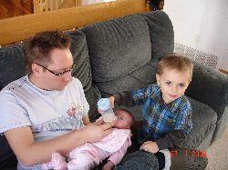 Félix est tout fier d'aider son papa à donner un biberon à sa petite sœur Chloé!
