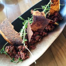 Kangaroo tartare with eschallots, capers, cornichons, chives and olive crisp