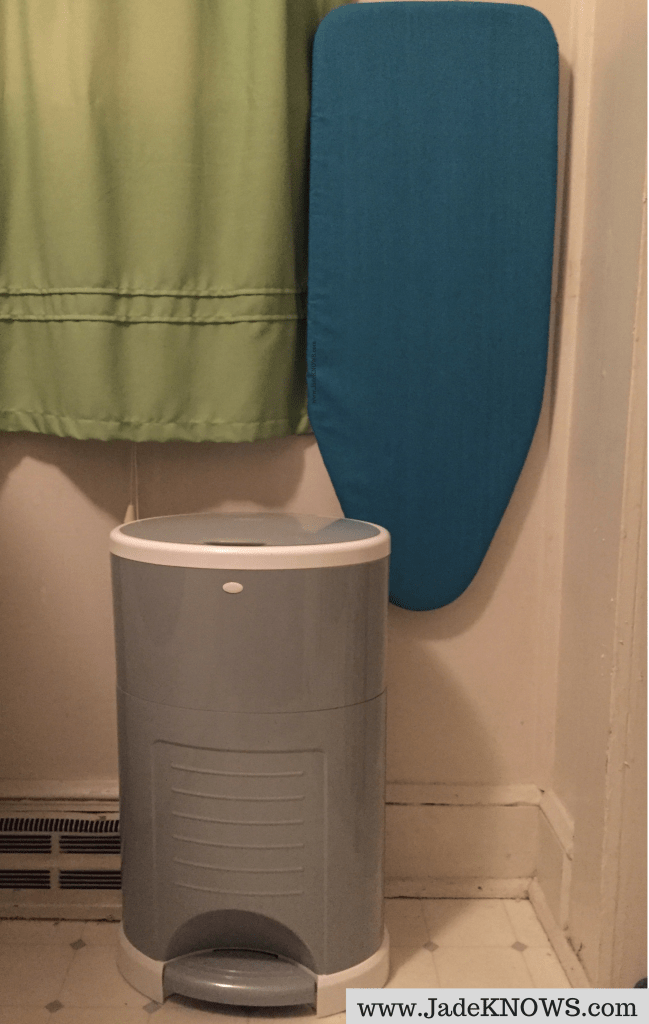 Gray Dekor Plus diaper pail sits beside a small blue ironing board hanging from a wall