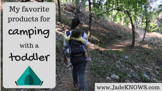 "Woman and toddler (viewed from behind) hike along a path using an Ergo 360 baby carrier. The text reads, ""My favorite products for camping with a toddler"" over a gray box, which also shows an image of a green tent."