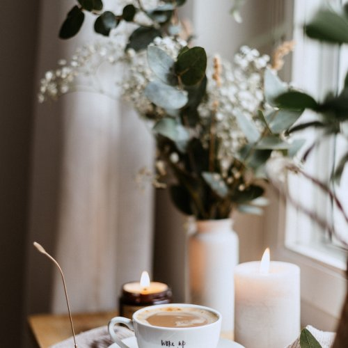 Flowers, burning candles and a cup of hot chocolate, sat on a wooden table