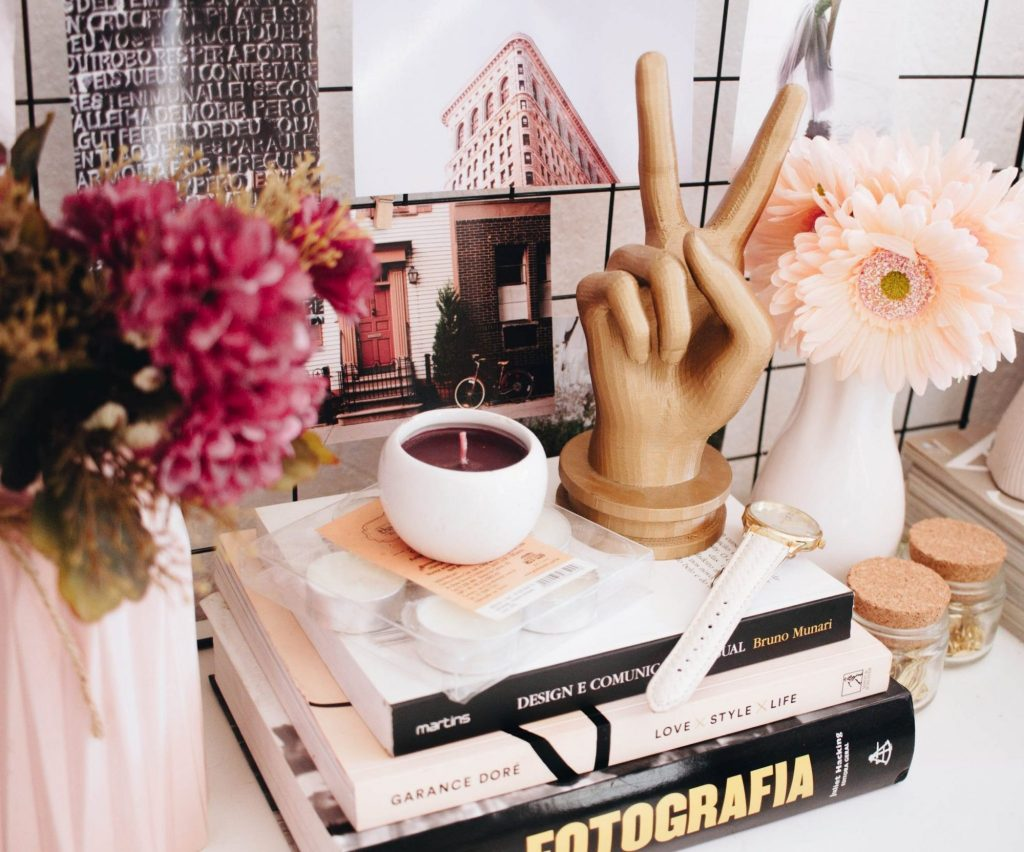 a candle and hand mannequin on top of a stack of books, on a slightly messy desk