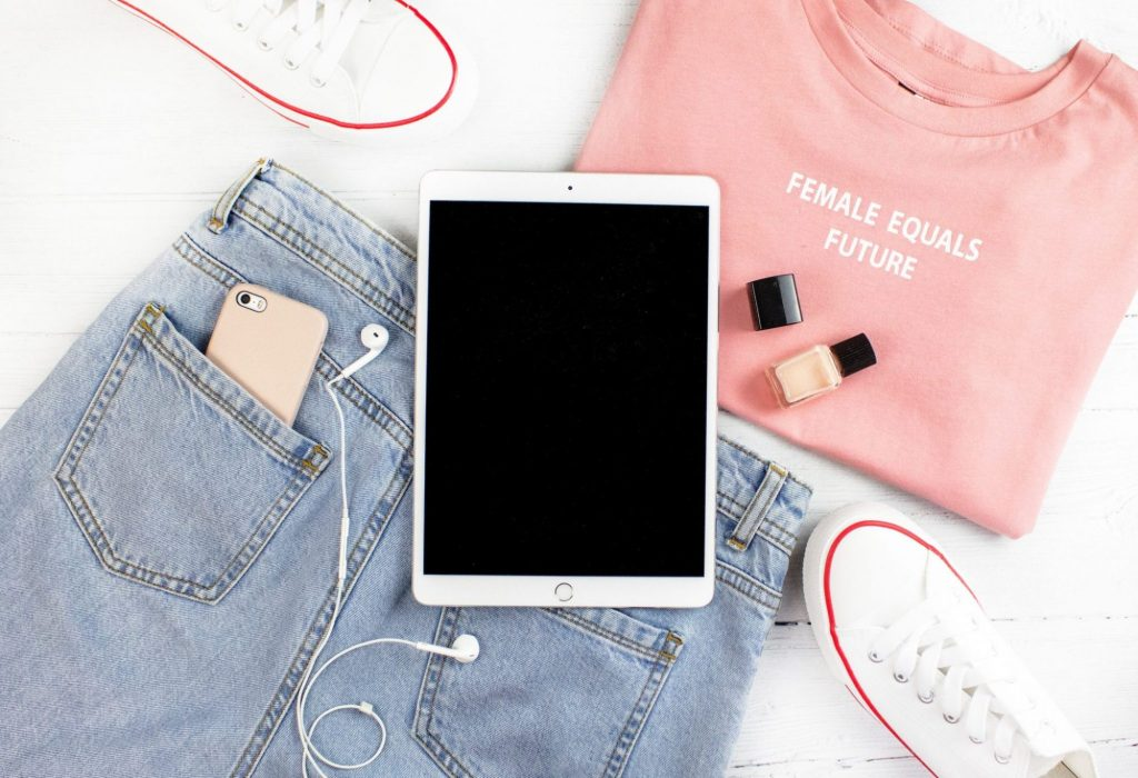 Pink t-shirt, blue jeans, iPhone, headphones, trainers and iPad flatlay