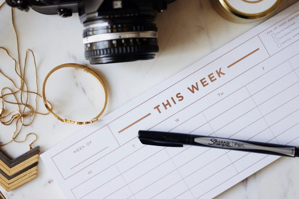 weekly planner with pen resting on top. Camera and metal bracelet half in shot
