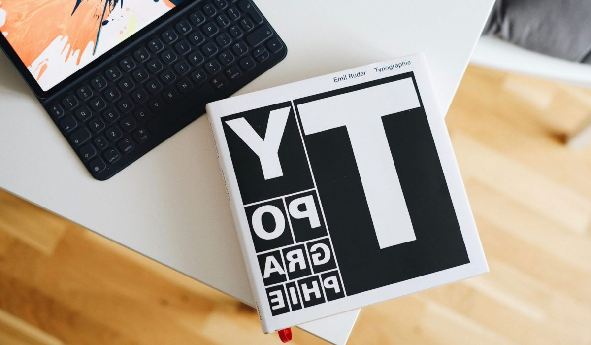 Typography book on the edge of a table, with an iPad Pro + magnetic keyboard next to it